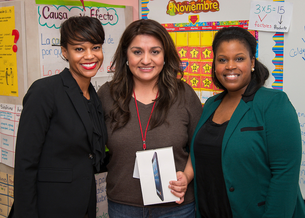 Elsa Simon, center, poses for a photograph after receiving an iPad Mini from Houston ISD Human Resource representatives Sherelle Foust, left, and Patra Brannon, right, for winning a drawing from teachers who referred newly hired teachers at Janowski Elementary School, November 25, 2013.