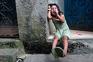 A young girl smiles in her doorway in the district of Belen in Iquitos, Peru.  Belen is situated south of the city center of Iquitos, on the bank of the Amazon River.  It is known for its high level of poverty and for the houses built to float as the river rises and recedes every year.
