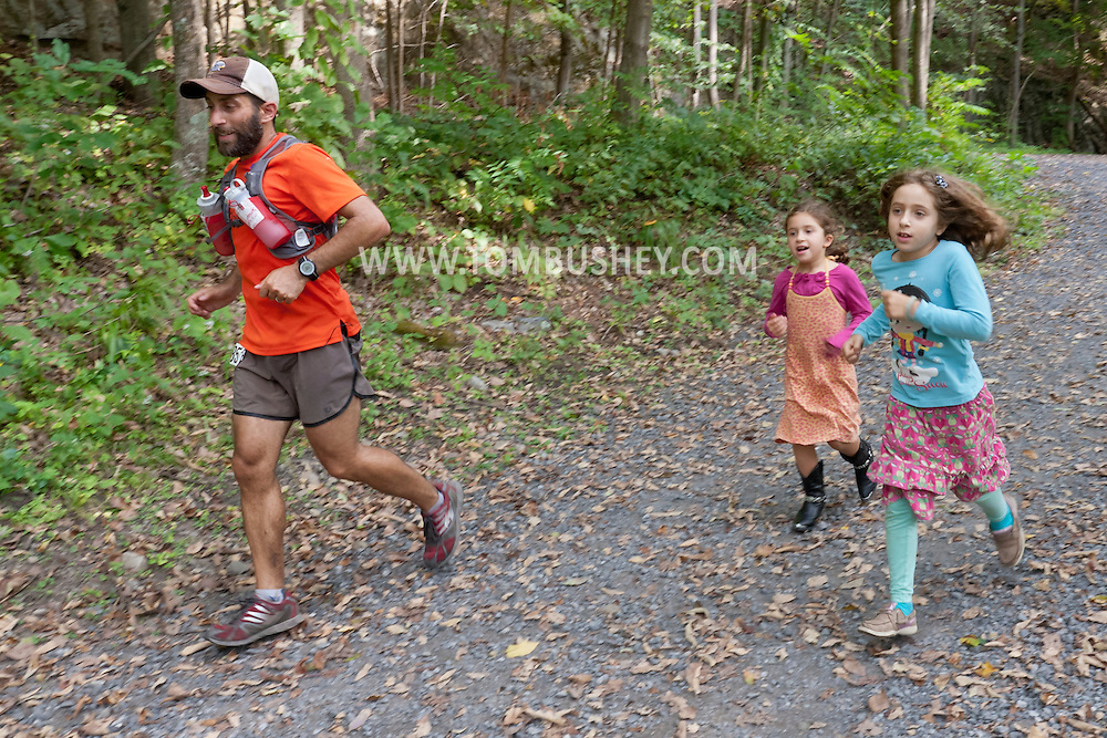 Rosendale, New York - Jason Friedman, escorted by his daughters, nears the finish line in the Shawangunk Ridge Trail Run/Hike 32-mile race on Sept. 20, 2014. Friedman finished second in six hours, 24 minutes.
