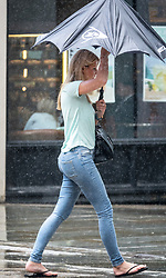 © Licensed to London News Pictures. 10/08/2018. London, UK. Shoppers run for cover as a sudden rain shower hits Uxbridge. Photo credit: Peter Macdiarmid/LNP