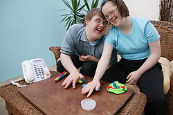 Teenage Downs Syndrome boy and girl playing with playdough,