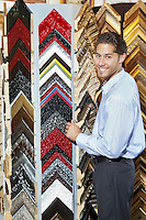 Portrait of a happy young man browsing at a frame store