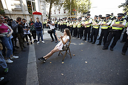 © Licensed to London News Pictures. 20/09/2019. London, UK. An activist taking part in the Global Climate Strike demonstration sits in a chair in front of a line of police blocking the road near Trafalgar Square. Thousands of similar actions are taking place all over the UK and the rest of the world. Photo credit: Peter Macdiarmid/LNP