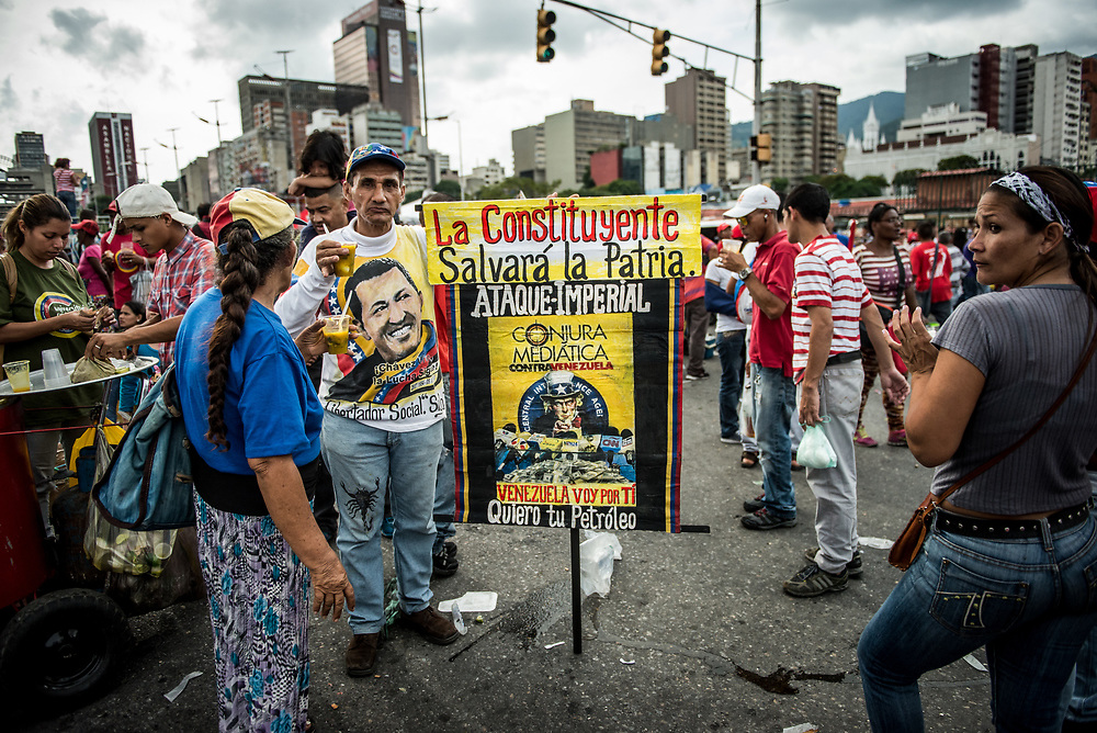 """CARACAS, VENEZUELA - JULY 27, 2017: A government supporter holds a sign with Uncle Sam being interviewed by international media, infront of a pile of dollars - that says, """"The Constituent will save the homeland"""" and """"Imperial attack""""  """"Media conspiracy against Venezuela"""" and """"I'm coming for you Venezuela, I want your oil""""  during the  final campaign rally for candidates for the election of the new constituent assembly, that will be held on July 30th. They marched and danced in the streets, as President Maduro and other socialist leaders addressed the large crowd. Opponents of the government criticize President Maduro for calling for this election - saying the new assembly is a power grab, and will be a puppet of the President - the only candidates on the ballot are government loyalists. Critics also fear the new assembly will re-write the constitution and wipe out the democratically elected and opposition controlled congress. There have been widespread reports of voter intimidation, and of the government threatening state workers and citizens that receive government benefits like subsidized food - who report the government telling them they are obligated to vote, and if they don't, they will lose their jobs and benefits. Thousands have taken to the streets to protest the election in the days leading up to the July 30th vote.  PHOTO: Meridith Kohut for The New York Times"""