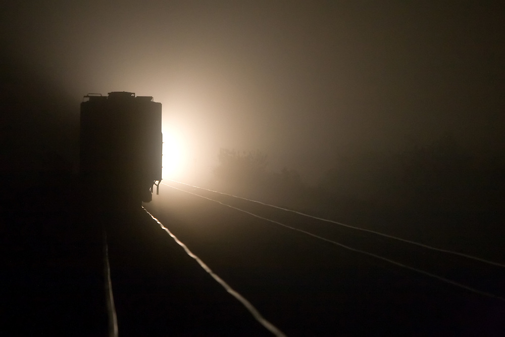 An approaching train lights up the surrounding countryside on a dense foggy night on the plains of Central Illinois.