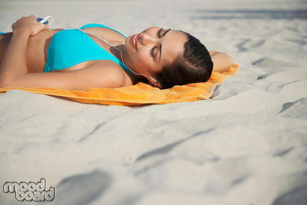 Teenage girl (16-17) using mp3 player lying on beach