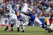 New York Jets quarterback Geno Smith (7) body snaps backwards as he releases a pass on a hard hit in the chest by diving Buffalo Bills defensive tackle Marcell Dareus (99) during the NFL week 11 football game against the Buffalo Bills on Sunday, Nov. 17, 2013 in Orchard Park, N.Y. The Bills won the game 37-14. ©Paul Anthony Spinelli