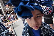 A young Japanese boy takes a break from helping to carry a mikoshi, or portable shrine, in the bi-annual Kanda matsuri (festival). Chiyoda Ward, Tokyo, Japan Sunday May 10th 2015. Over 200 mikoshi are carried through the streets of central Tokyo every 2 years in this spring festival