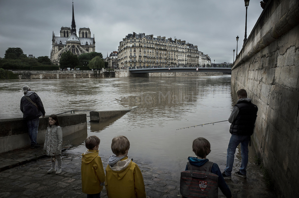 Swollen river Seine raises Paris in high alert as water raise to record levels.  Seen from Saint Louis island, Parisians wander on the flooded banks with Notre Dame cathedral on the Ile de la Cite in the background. 03 June 2016.