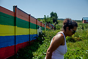 """The wall at the Roma settlement Ostrovany seen from the settlement. Veronika a Roma woman herself at the wall,""""I live in the settlement. I work as assistant at the town hall. The fence is not dividing us in anything, we did not go to the gardens  anyway - sometimes some children were jumping over to get some fruits. There were other fences before. Children, not adults. I feel it is like a fence and not a wall. It is a normal solution. I understand the owners who had a problem with this. I would save also my property…that is normal."""""""