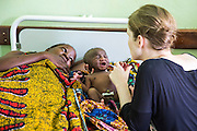 Dr Siobhan Neville and Dr Godfrey Kambanga examine a baby with a cleft palette on the children's ward during the daily rounds. The baby had not been feeding properly. due to its condition. St Walburg's Hospital, Nyangao. Lindi Region, Tanzania.