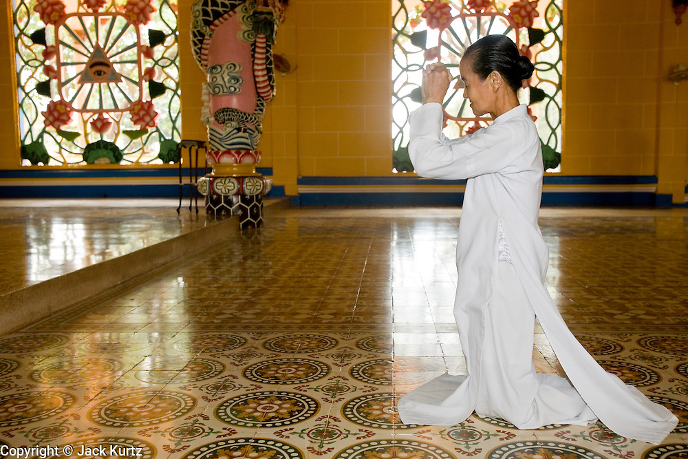 "10 MARCH 2006 - TAY NINH, VIETNAM: Women praying in the main Cao Dai Temple in Tay Ninh. The Cao Dai complex in Tay Ninh is the sect's headquarters. The Cao Dai religion is a blending of Buddhism, Confucianism, Taoism, Christianity and Islam. There ""saints""  include Chinese leader Sun Yat Sen and French author Victor Hugo. There are about two million members of the Cao Dai religion in Vietnam. British author Graham Greene, who wrote about the Cao Dai in the ""The Quiet American"" said the relegion was ""a Walt Disney fantasia of the East."" Photo by Jack Kurtz / ZUMA Press"