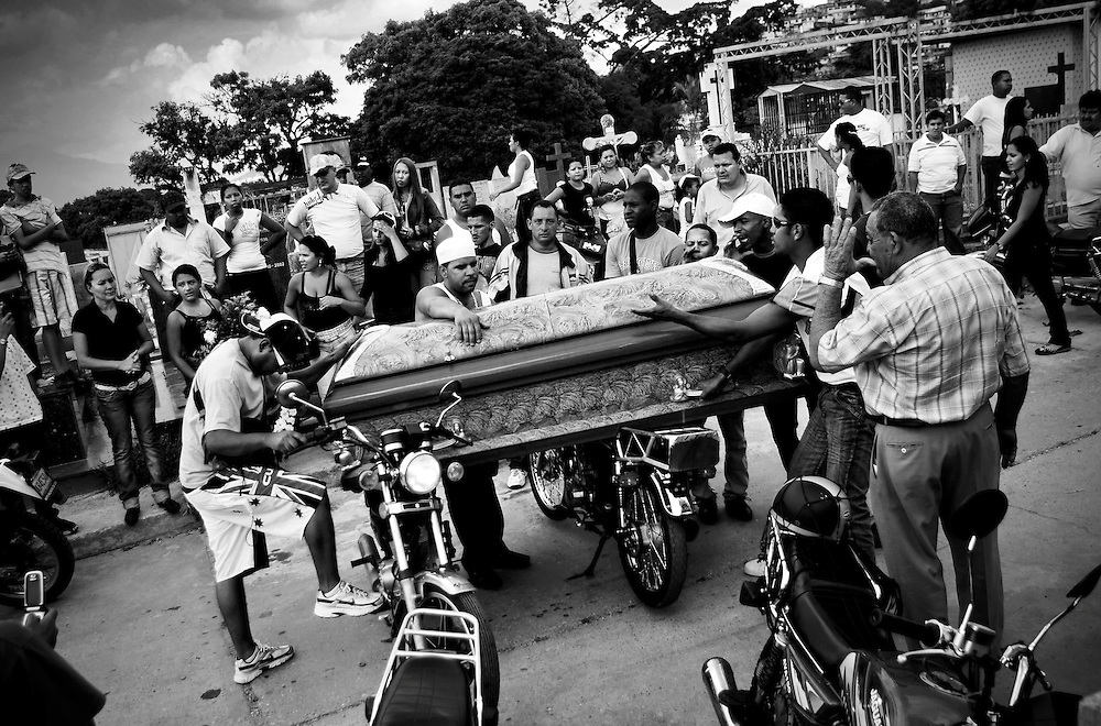 Family and friends pay homage to a young man murdered in the La Pastora slum in Caracas, Venezuela by resting his casket on motorcycles at the cemetery before his burial.