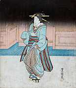 Geisha on an evening stroll in Fukagawa, c1830.  Utagawa Toyokuni (c1777-1835) Japanese Ukiyo-e artist. Geisha with traditional hairstyle in blue kimono, wearing pattens, holding robe to avoid ground.  Entertainer Female