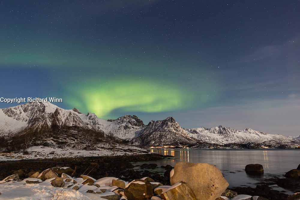 Aurora Borealis or Northern Lights over mountains, viewed from near Ørsnes in the Lofoten Islands of Norway.