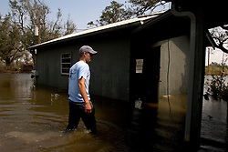25 Sept, 2005.  Carlyss, Louisiana.  Hurricane Rita aftermath. <br /> Local cajun man Aaron Stokes checks on a family property ravaged by the storm as he tours the swamps and bayou's checking on neighbours and their homes.<br /> Photo; ©Charlie Varley/varleypix.com
