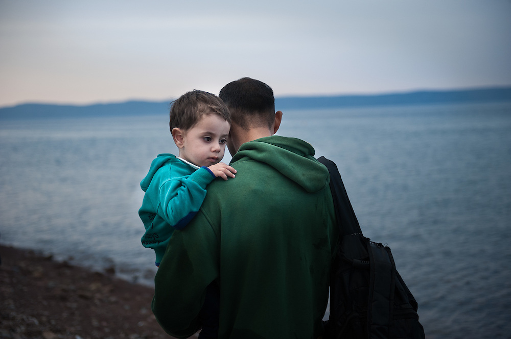 A Syrian father carrying his son, that just landed in the Greek island of Lesvos walks towards the nearest police station to report their arrival and get registered. Near Skala Sikamineas, Lesvos , Greece