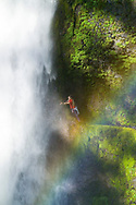 A young woman, enjoys a beautiful rainbow and the spray of water from Tunnel Falls on Eagle Creek trail in Hood River County, Oregon, USA.  Tunnel Falls received its name due to a tunnel being cut from the bedrock behind the falls so that hikers and trail runners can pass further up the gorge.  The trail becomes very narrow during this section and it is necessary to hold onto a safety cable. (Model Released)