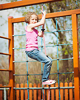 Young girl climbing rope in playground