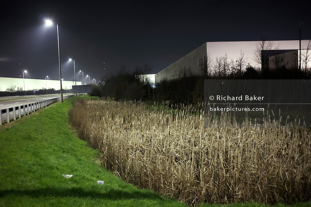 Alongside the A5 highway, an industrial landscape is illuminated in light from roadside street-lighting. Reeds are in the foreground in front of a giant generic warehouse that glows from its own territory. Grass is next to the crash-barrier and faint mist is seen on this cold winter night at the DIRFT warehouse logistics park in Daventry, Northamptonshire England. This 365 acre site off Junction 18 of the M1 motorway is a hub for road, rail and service infrastructure, some 2.3m sq.ft. of distribution and manufacturing floorspace had been constructed by 2004 and occupiers including Tesco?s, Tibbett & Britten plc, Ingram Micro, Royal Mail, the W.H. Malcolm Group, Eddie Stobart Ltd, Wincanton and Exel, have been attracted to this unique logistics location.