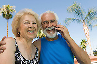 Senior Couple Using Cell Phone Outside