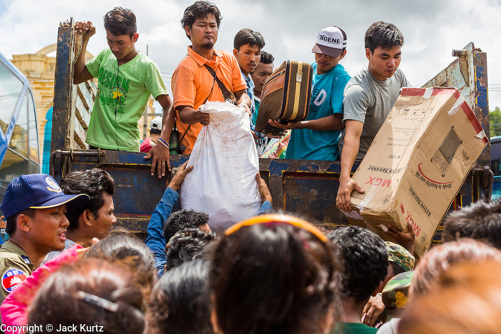 16 JUNE 2014 - POIPET, CAMBODIA: Cambodian migrants unpack a truck full of their belongings after they returned to Poipet, Cambodia from Thailand. More than 150,000 Cambodian migrant workers and their families have left Thailand since June 12. The exodus started when rumors circulated in the Cambodian migrant community that the Thai junta was going to crack down on undocumented workers. About 40,000 Cambodians were expected to return to Cambodia today. The mass exodus has stressed resources on both sides of the Thai/Cambodian border. The Cambodian town of Poipet has been over run with returning migrants. On the Thai side, in Aranyaprathet, the bus and train station has been flooded with Cambodians taking all of their possessions back to Cambodia.  PHOTO BY JACK KURTZ