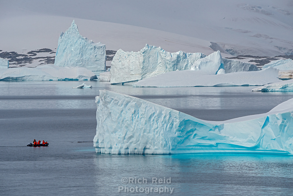 Zodiac among the ice in Port Charcot taken from Booth Island in the Wilhelm Archipelago of Antarctica.