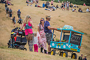 A young child is pushed round by dedicated parents in a home made trolley for the festival - The 2017 Glastonbury Festival, Worthy Farm. Glastonbury, 2 June 2017
