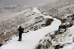 © Licensed to London News Pictures. 22/01/2019. Snowdonia, Gwynedd, Wales, UK.  A hiker sets off to climb Mount Snowden as snow showers continue in Snowdonia National Park, Gwynedd, UK. credit: Graham M. Lawrence/LNP