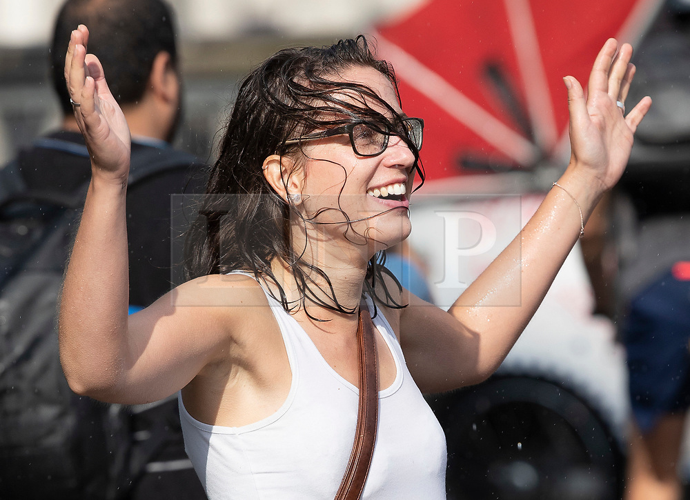 © Licensed to London News Pictures. 27/07/2018. London, UK. A woman reacts after getting caught in a sudden downpour near Parliament as rain breaks the heatwave. Photo credit: Peter Macdiarmid/LNP