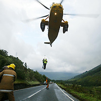 RAF rescue helicopter winch stranded people from their vehicles after a landslide engulfed the A84 north of Lochearnhead<br /><br />Picture by John Lindsay<br />Copyright Perthshire Picture Agency<br />Tel: 01738 623350  Mobile: 07775 852112
