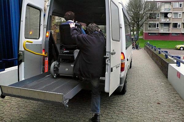 Nederland, Nijmegen, 6-12-2007..Een oudere vrouw in een electrische rolstoel wordt in een taxi geholpen door de chauffeur...Foto: Flip Franssen