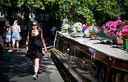 © Licensed to London News Pictures. 24/07/2018. London, UK. A commuter walks past a canalboat in Little Venice in central London, as warm temperatures in the capital continue. Forecasters are predicting record temperatures later this week. Photo credit: Ben Cawthra/LNP