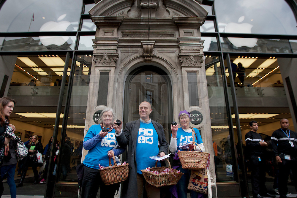 © licensed to London News Pictures. London, UK 25/04/2012. Greenpeace activists handing out black apples to demonstrate against Apple's polluting coal usage to power their data centres, outside Regent Street Apple Store, this afternoon (25/04/12). Photo credit: Tolga Akmen/LNP