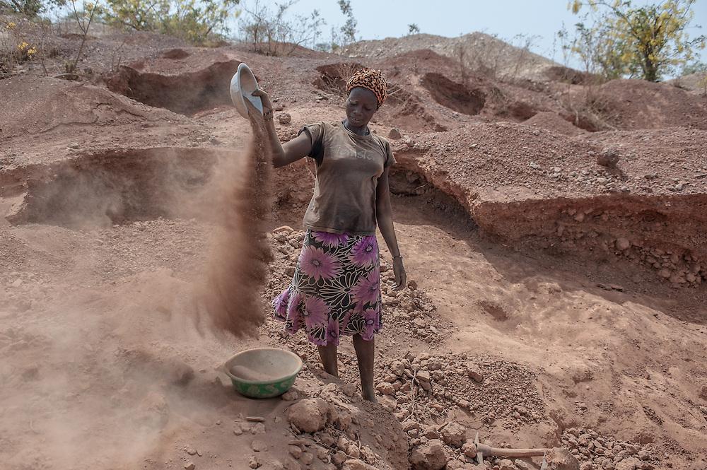 """Noelie, 18 anni, setaccia la terra a pochi metri dalla principale vena mineraria nella miniera d'oro artigianale di Nobsin in Burkina Faso il 13 Maggio 2014. Prima di lavorare nelle miniere, Noelie produceva una bevanda a base di miglio chiamata zom koom che vendeva al mercato locale. """"Adesso guadagno in media 10/15.000 CFA al mese"""" racconta, piegando il setaccio con un movimento circolare per separare le pietre dalla terra. """"Sono contenta di essere riuscita a comprarmi una nuova bicicletta, così ogni sera posso tornare a dormire a casa insieme ai miei genitori, a Pinsega, 20 km da qui. """"E' un lavoro faticoso, tutto il giorno sotto il sole. Spero un giorno di aprire un piccolo negozio di alimentari"""""""