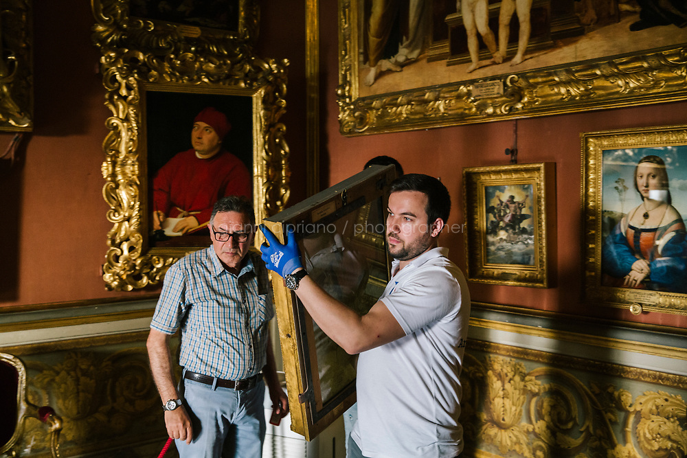 FLORENCE, ITALY - 3 JUNE 2018: Museum technicians are seen here in the Hall of Saturn at Palazzo Pitti as they start transporting the dual portraits of Agnolo Doni and his wife Maddalena Strozzi, painted by Raphael, to their new location at room 41 of the Uffizi, in Florence, Italy, on June 3rd 2018.<br /> <br /> As of Monday June 4th 2018, Room 41 or the &ldquo;Raphael and Michelangelo room&rdquo; of the Uffizi is part of the rearrangement of the museum's collection that has<br /> been defining Uffizi Director Eike Schmidt&rsquo;s grander vision for the Florentine museum.<br /> Next month, the museum&rsquo;s Leonardo three paintings will be installed in a<br /> nearby room. Together, these artists capture &ldquo;a magic moment in the<br /> first decade of the 16th century when Florence was the cultural and<br /> artistic center of the world,&rdquo; Mr. Schmidt said. Room 41 hosts, among other paintings, the dual portraits of Agnolo Doni and his wife Maddalena Strozzi painted by Raphael round 1504-1505, and the &ldquo;Holy Family&rdquo;, that Michelangelo painted for the Doni couple a year later, known as the<br /> Doni Tondo.