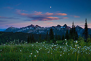 The Tatoosh Range in Washington state is framed by the nearly full moon, red clouds and summer flowers. This image was captured from the Skyline Trail in Mount Rainier National Park.