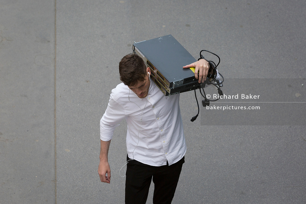 A man carries electronic equipment on his shoulder in the City of London - the capital's financial district, on 21st August 2018, in London, England.