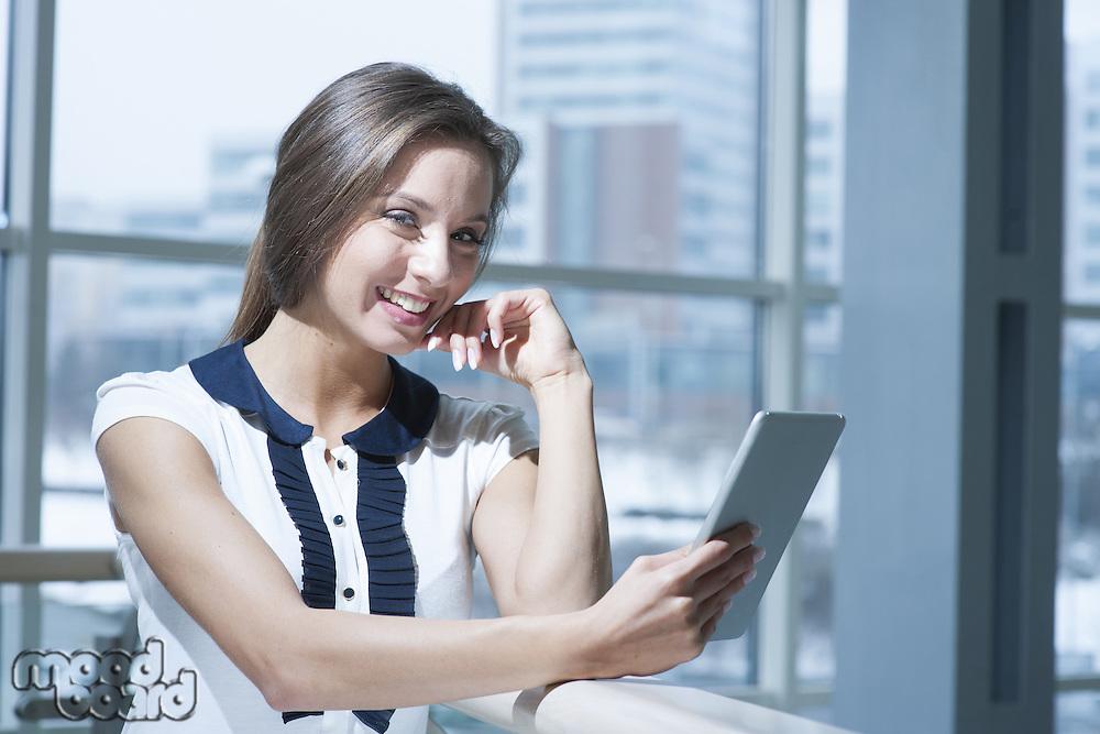 Pensive businesswoman smiling at camera holding digital tablet