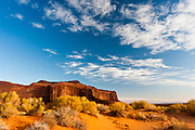White cirrus clouds hover over one of the many Mesas in Monument Valley Navajo Tribal Park