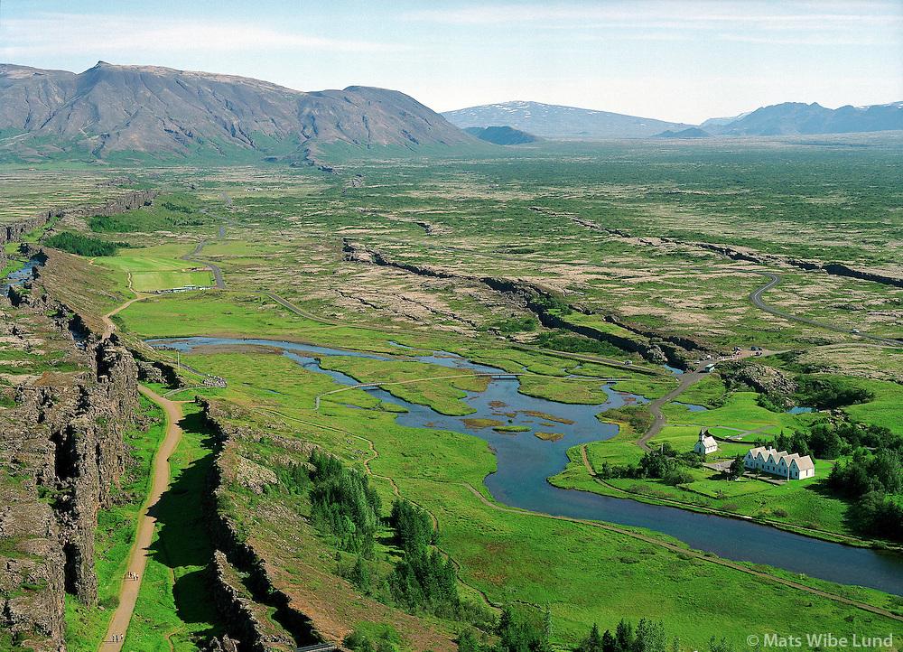 Þingvellir / Thingvellir, Almannagjá / Almannagja earthquake rift in foreground left. River Öxará / Oxara and the priesters fram and church right in picture. Aerial..Þingvallahreppur