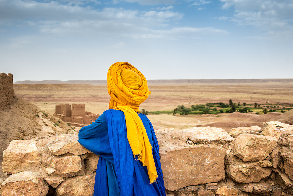 A Tuareg guide stares at the horizon at the fortress on top of the hill overlooking Aït Benhaddou. This city, sited in Morocco, on the road from Marrakech to Sahara, has become famous for having staged several Hollywood blockbuster movies including the Gladiator and the Passion of Christ, and is protected by UNESCO as a world heritage site.