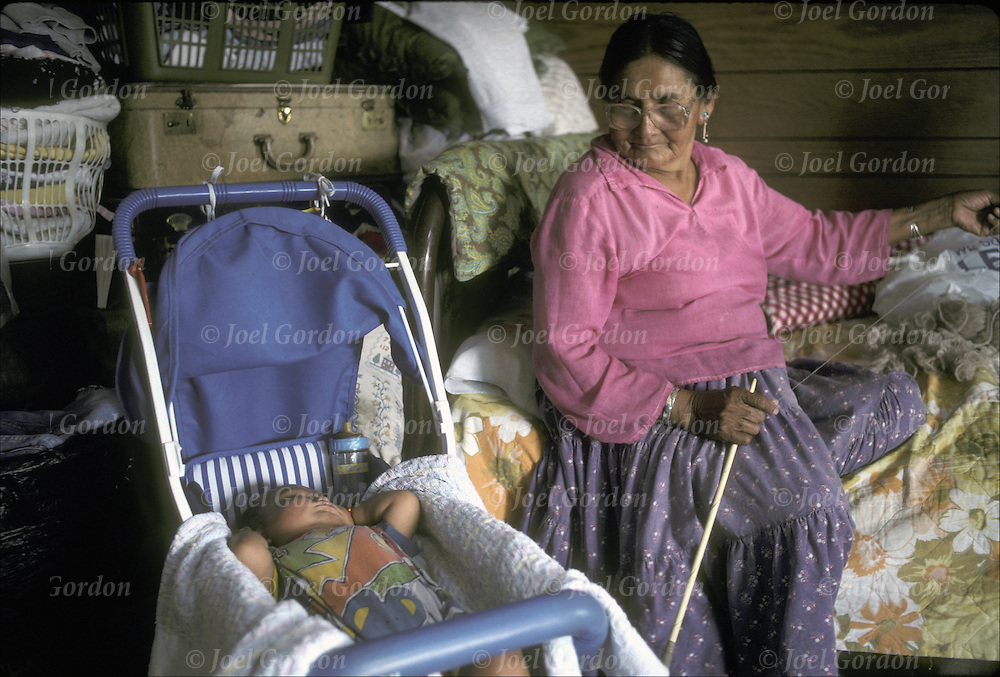 Virgina Deal, Native American Navajo grandmother watching over toddler grandchild, as she spins wool to weave rug in hogan,Navajo Reservation, Newcomb, NM