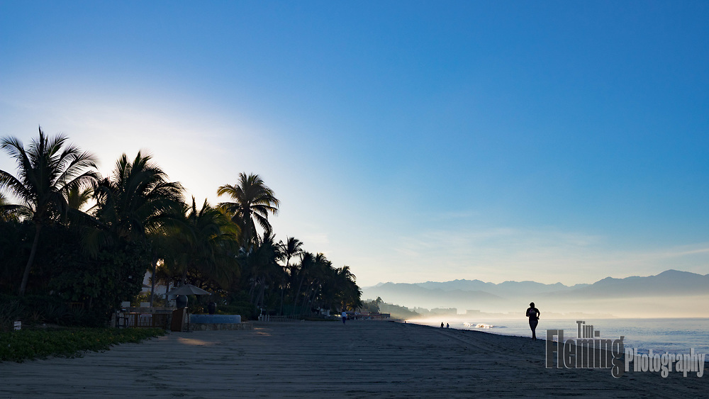 Jogger on the beach at sunrise in Bucerias, Nayarit, Mexico.
