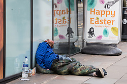 © Licensed to London News Pictures . 03/04/2017 . Manchester , UK . A man lies slumped outside a branch of Sainsburys on Mosley Street , in the middle of the day , beside street furniture advertising a Happy Easter , in Manchester City Centre . The city has experienced a growth in the number of people sleeping rough and emergency services report spikes in the need to tend to people high on Spice . Photo credit : Joel Goodman/LNP
