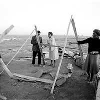 Ivory Park, South Africa, Aug 1991.  A woman is helped to erect a temporary shelter for the night after police demolished the illegal shack she erected near Tembia, Transvaal, some 15km from Johannesburg. (Photo by Greg Marinovich)