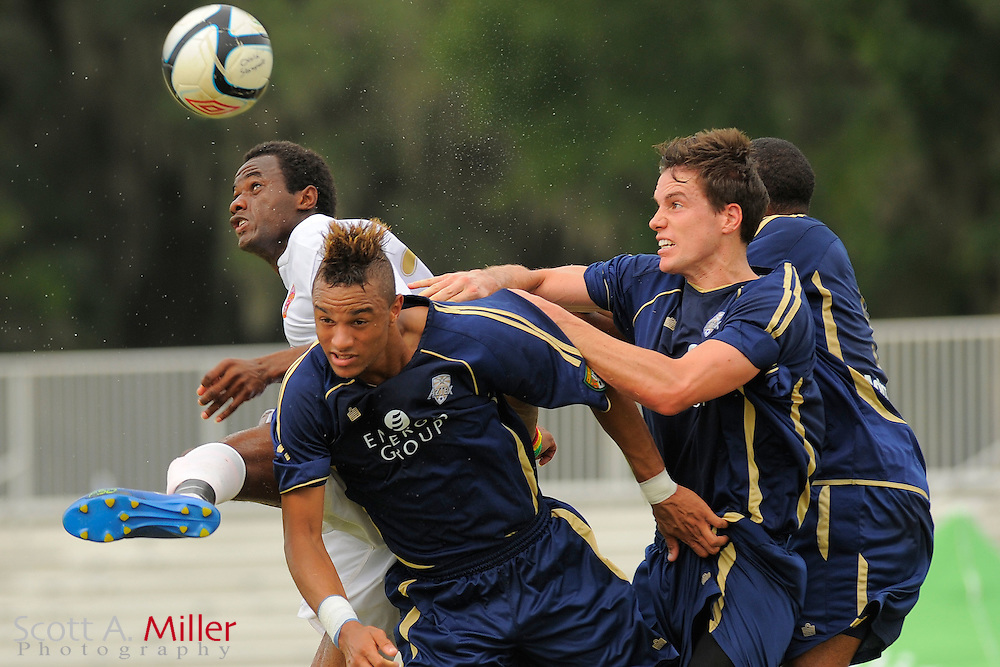 Orlando City defender Oumar Diakhite (25) goes airborne for a ball with Austin Aztex forward Khiry Shelton (20), defender Ross Kelly (31) and Austin Aztex midfielder Jacob Powell (9) in City's 4-2 win in the PDL Southern Conference Championships final at Trinity Catholic High Schooll on July 22, 2012 in Ocala, Florida. ..©2012 Scott A. Miller