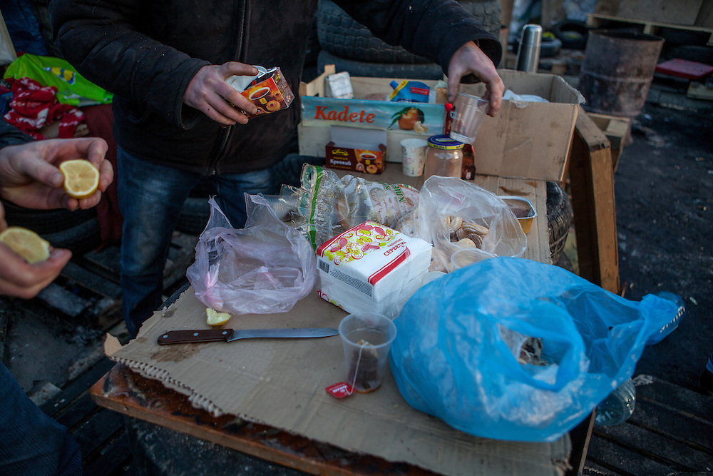 "Table with food supplies at the barrikades blockading a building supplies store named ""Epicenter"" in the city of Lviv, Ukraine. Two people passing by."