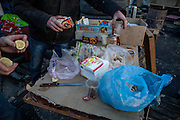 """Table with food supplies at the barrikades blockading a building supplies store named """"Epicenter"""" in the city of Lviv, Ukraine. Two people passing by."""