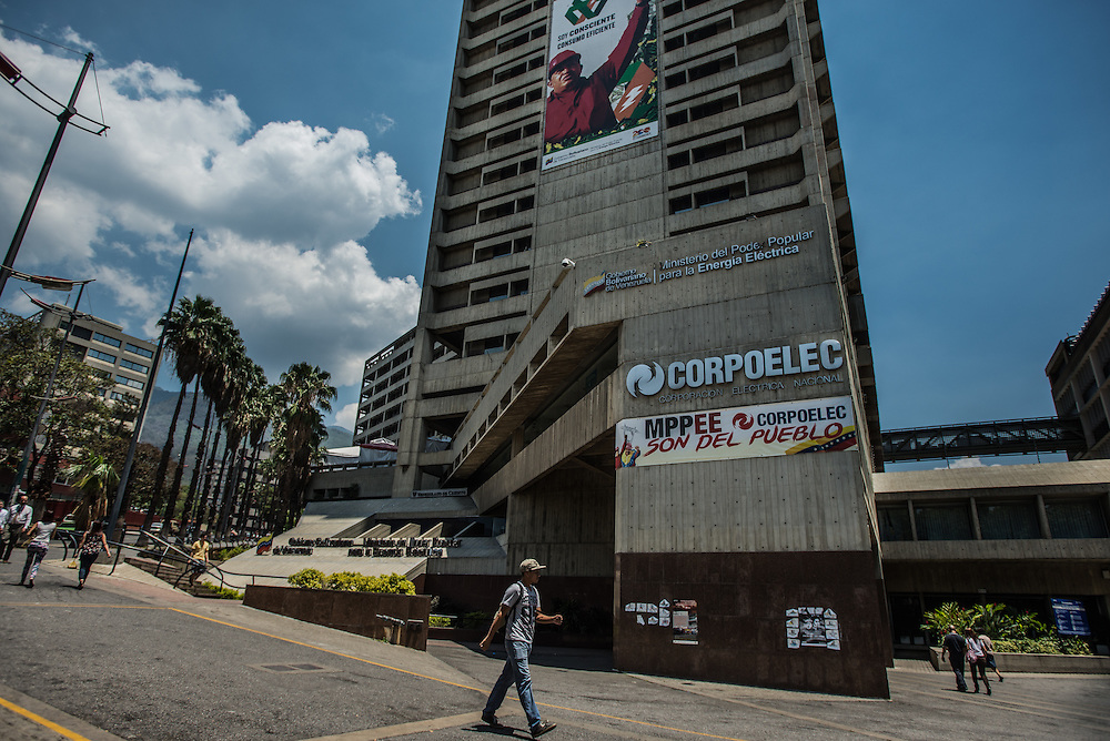"""CARACAS, VENEZUELA -MARCH 21, 2016: People walk past the headquarters of Corpoelec, the state power corporation of Venezuela in downtown Caracas.  A multiple-story high government propaganda sign hangs from the building with a photo of late President, Hugo Chávez wearing a hardhat, and says in Spanish: """"I am conscientous, I consume efficiently"""". Venezuela is shutting down this week, as the government struggles with a deepening electricity crisis.  President Nicolas Maduro gave everyone an extra three days off work, extending the two-day Easter holiday, according to a statement in the Official Gazette published late last Tuesday.  The government has rationed electricity and water supplies across the country for months and urged citizens to avoid waste as Venezuela endures a prolonged drought that has slashed output at hydroelectric dams. The ruling socialists have blamed the shortage on the El Nino weather phenomena and """"sabotage"""" by their political foes, while critics cite a lack of maintenance and poor planning.  PHOTO: Meridith Kohut for Bloomberg News"""